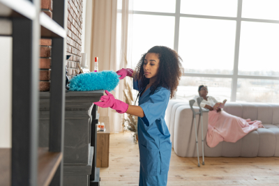 caregiver wearing pink gloves dusting the fireplace in the living room