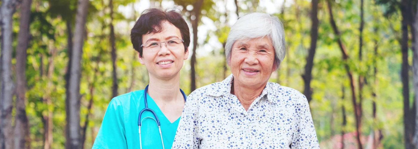 female nurse wearing eyeglasses and senior woman smiling